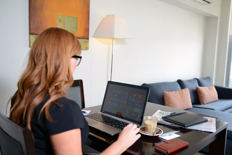 corporate traveler in apartment on laptop